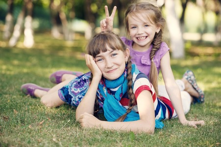 Funny girls laying on the grass photo