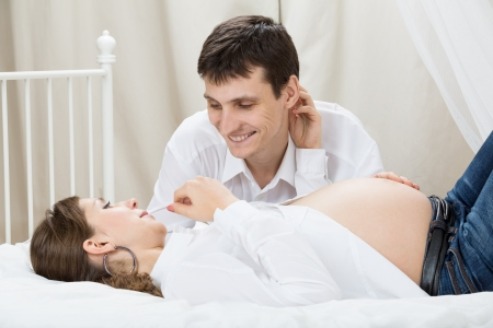seven persons: Portrait of a man touching the belly of his pregnant wife lying on their bed