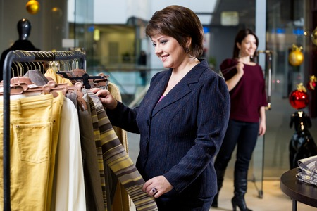 shopaholism: two happy women shopping in clothes store Stock Photo