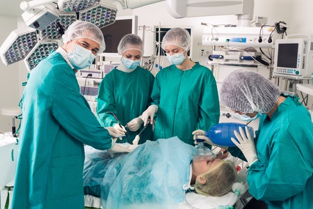 Surgeon looking at camera with colleague performing in background photo