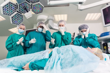 surgical department: surgeons in operative room above dead patient