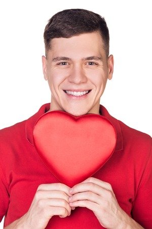 A smiling young male holding a red heart shaped box isolated on white background photo