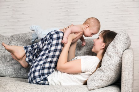 Happy mother playing with her cute loving baby at home photo