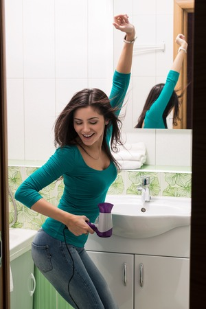 A young woman drying hair in front of a bathroom mirror. Vertical shot.
