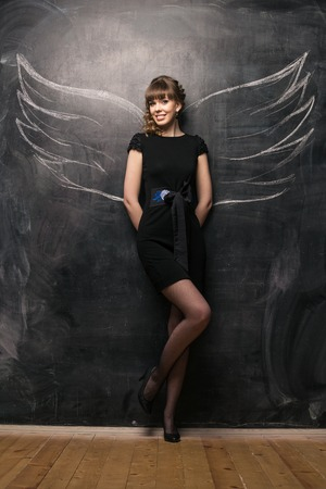 girl over chalkboard with funny angel wings photo