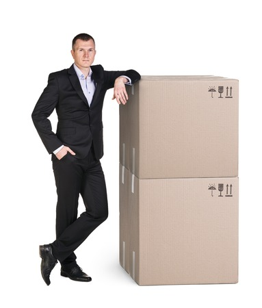 pasteboard: Manager in suit stands near pile of pasteboard boxes, isolated on white Stock Photo