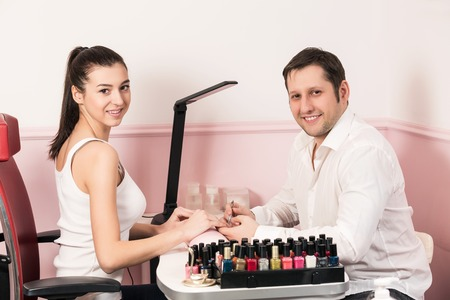 Man manicurist doing manicure for woman in beauty salon