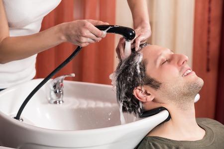 haircutter: Washing man hair in beauty parlour hairdressing salon Stock Photo