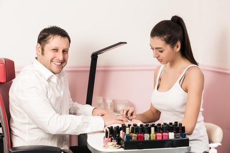 manicurist: Beautiful girl manicurist doing manicure for man in beauty salon