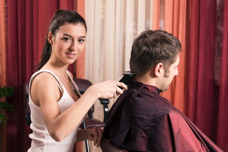 haircutter: The beautiful young woman the hairdresser does a  hairstyle to the client - young man