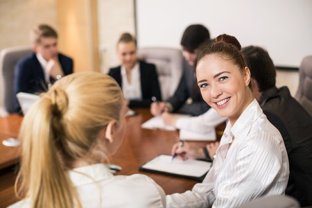 Confident beautiful female team leader sitting in a business meeting at a table with a group of her colleagues turning to smile at the camera, selective focus photo