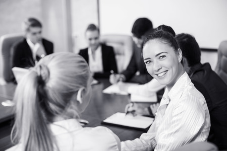 turning table: Confident beautiful female team leader sitting in a business meeting at a table with a group of her colleagues turning to smile at the camera, selective focus
