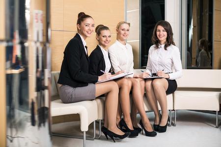 Vier mensen in de lobby schrijven op het klembord glimlachen