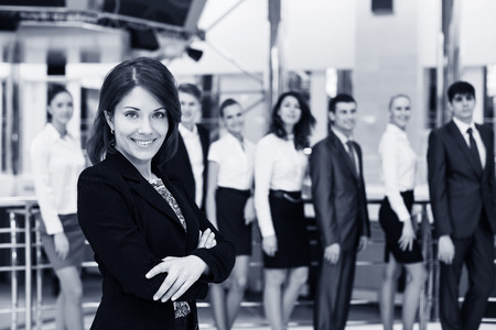 Confident in herself. Cheerful mature woman in formalwear keeping arms crossed and smiling while her colleagues talking on background photo