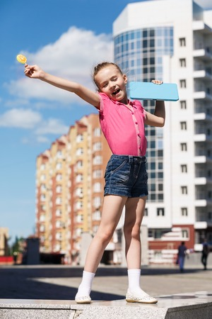 Little girl with candy lollipops on city background Stock Photo