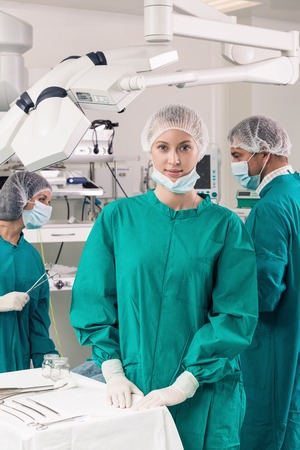 Surgeons with instruments looking at camera with colleagues performing in background