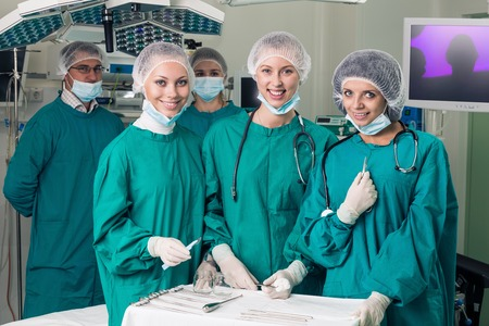 Surgeons with instruments looking at camera with colleagues performing in background photo