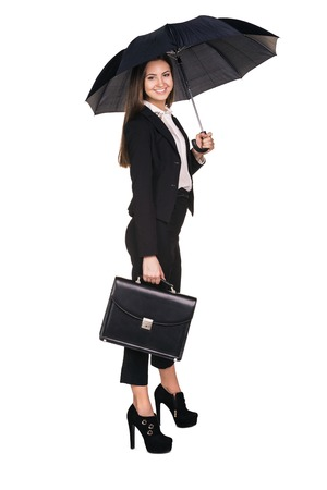 Attractive smiling business woman holding up a black portfolio case and an umbrella with one leg up standing on one foot on white background photo