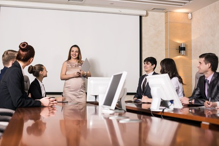 Pregnant business consultant answering a question during a meeting at office photo