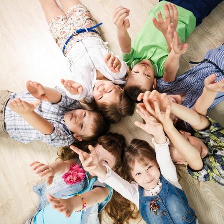 Gruppo di bambini felici posa a forma di stella sul pavimento con le mani alzate Archivio Fotografico