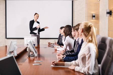 attend: Business consultant answering a question during a meeting at office