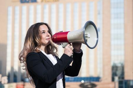 Stylish businesswoman holding a megaphone outdoors photo