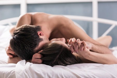Sex: young lovers kissing on the bed focused on hand