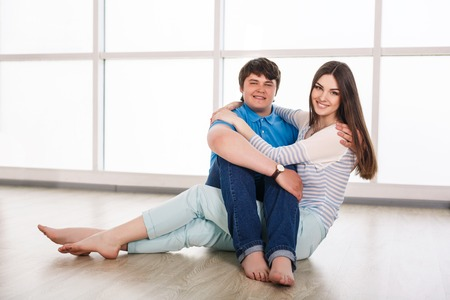 25 30 years: Attractive young adult couple sitting close on floor in home smiling and laughing