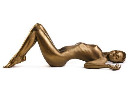 ゴールデンの健康な皮膚と光沢のあるモデルのバルキリー概念芸術家気取り肖像画の黄金像まつげ完璧なスポーティなボディ スタジオ撮影
