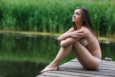 Beautiful young nude woman outdoors portrait on the lake