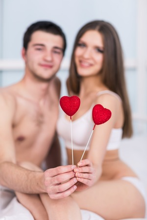 man flying: love valentine day couple holding red heart young lovely together lying in a bed, happy smile looking at camera, concept hearts flying around Stock Photo