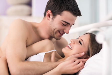 sex activity: Beautiful young loving couple lying in bed