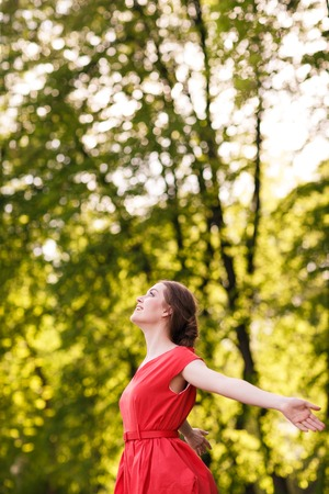 Adorable summer young woman in red dress, carefree dancing enjoying nature photo