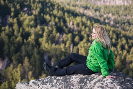 Young woman sitting on a rock and looking to the clouds  photo