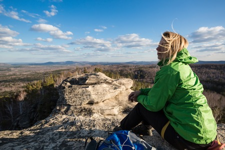 Beautiful woman sitting on top of a mountain and enjoying the view photo
