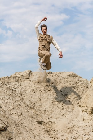 Young man jumping happy in the desert photo