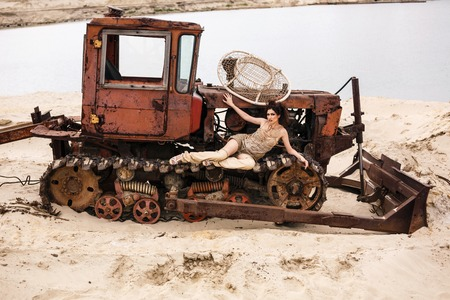 Sexy fashion model lying on a tractor in the desert photo