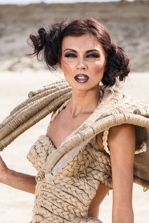 Fashionable young attractive and sensuality brunette woman in dress on the desert photo