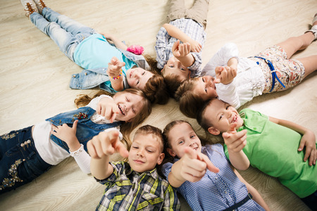 lifted hands: Group of happy kids laying in star shape on the floor with lifted hands