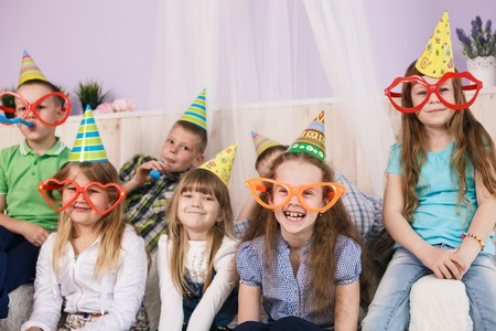 Large group of diversity looking kids, boys and girls sitting on the couch at home, hugging, smiling and laughing photo