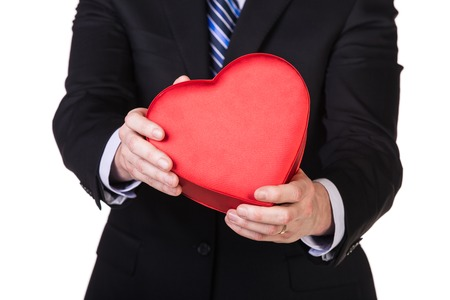 Elegant man in suit giving box heart isolated on white photo