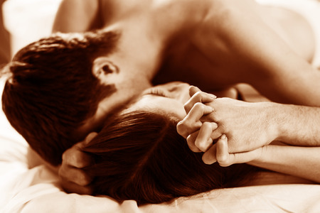 erotic couple: young lovers kissing on the bed focused on hand