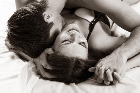 man and woman sex: молодые любители целоваться на кровати сосредоточены на руках Фото со стока