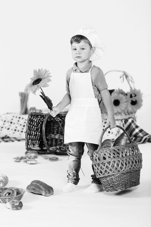 Little boy chef stands wih a basket and flower in his white chefs uniform photo