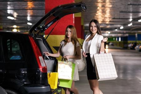 carro supermercado: Dos jóvenes compradores en un aparcamiento Foto de archivo