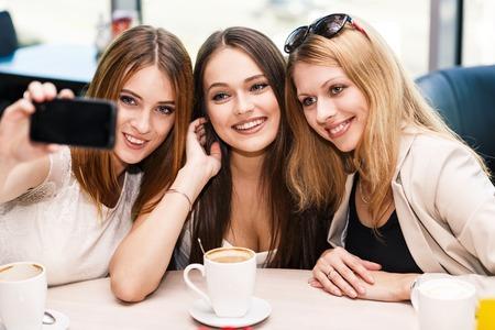 tomando refresco: Vacaciones - hermosas chicas que toman el cuadro en el café