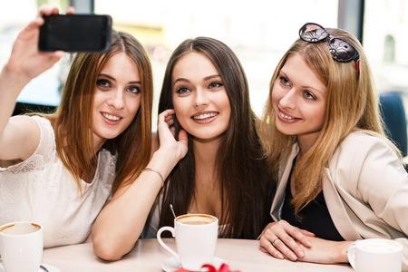 tomando refresco: Vacaciones - hermosas chicas que toman el cuadro en el caf�