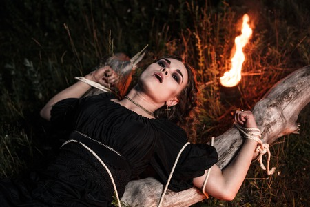 midwinter: Beautiful young witch in the flames of fire Stock Photo