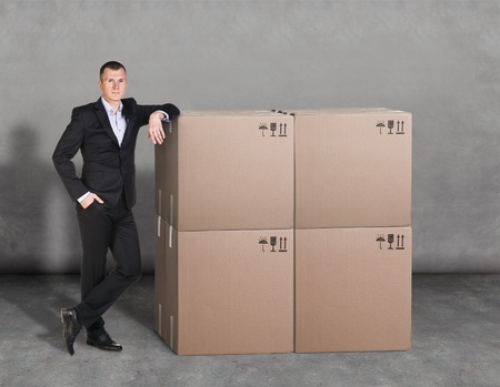 pasteboard: Manager in suit stands near pile of pasteboard boxes Stock Photo