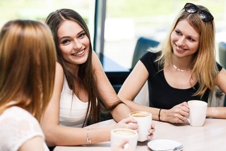 Glückliche Frauen, die Kaffeetasse, während sucht bei jedem anderen in cafe